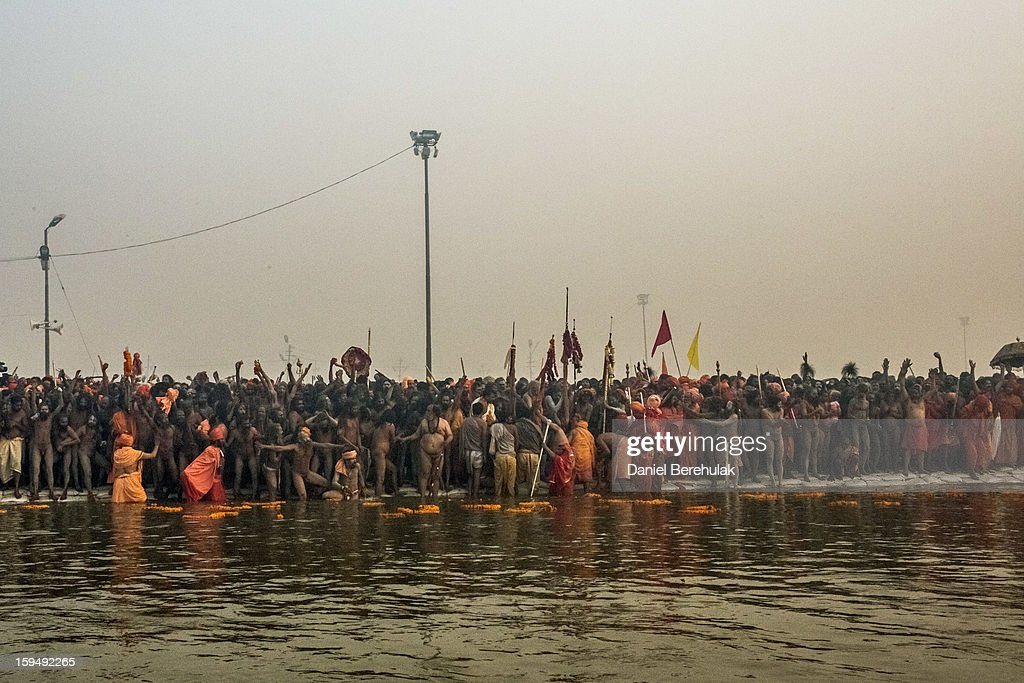 Naga sadhus line up along the banks of Sangam, the confluence of the holy Ganges and Yamuna rivers during the auspicious bathing day of Makar Sankranti , the start of the Maha Kumbh Mela on January 14, 2013 in Allahabad, India. The Maha Kumbh Mela, believed to be the largest religious gathering on earth is held every 12 years on the banks of Sangam, the confluence of the holy rivers Ganga, Yamuna and the mythical Saraswati. The Kumbh Mela alternates between the cities of Nasik, Allahabad, Ujjain and Haridwar every three years. The Maha Kumbh Mela celebrated at the holy site of Sangam in Allahabad, is the largest and holiest, celebrated over 55 days, it is expected to attract over 100 million people.