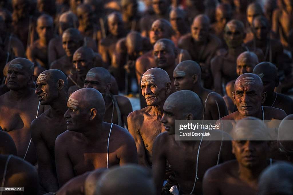 Naga sadhus, naked Hindu holy men, sit during an initiation ceremony on the banks of the Ganges river during the Maha Kumbh Mela on February 8, 2013 in Allahabad, India. The Maha Kumbh Mela, believed to be the largest religious gathering on earth, is held every 12 years on the banks of Sangam, the confluence of the holy rivers Ganga, Yamuna and the mythical Saraswati. The Kumbh Mela alternates between the cities of Nasik, Allahabad, Ujjain and Haridwar every three years. The Maha Kumbh Mela celebrated at Sangam, is the largest and holiest, celebrated over 55 days, and is expected to attract over 100 million pilgrims who will bathe in holy waters to wash away their sins.