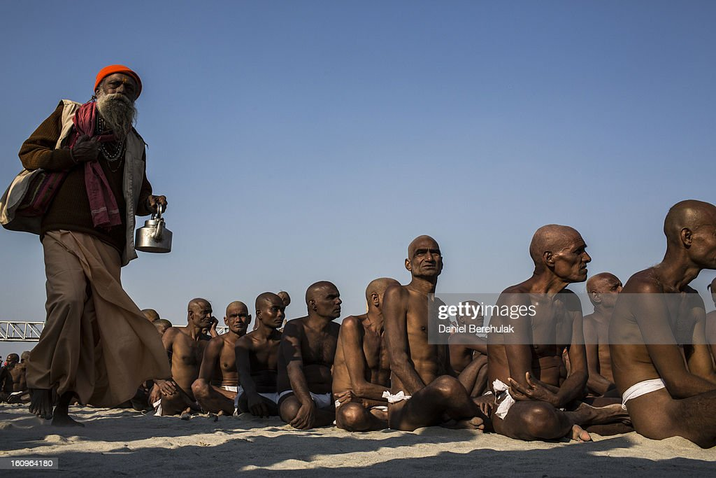 Naga sadhus, naked Hindu holy men, wait for food during their initiation ceremony on the banks of the Ganges river during the Maha Kumbh Mela on February 8, 2013 in Allahabad, India. The Maha Kumbh Mela, believed to be the largest religious gathering on earth is held every 12 years on the banks of Sangam, the confluence of the holy rivers Ganga, Yamuna and the mythical Saraswati. The Kumbh Mela alternates between the cities of Nasik, Allahabad, Ujjain and Haridwar every three years. The Maha Kumbh Mela celebrated at Sangam, is the largest and holiest, celebrated over 55 days, and is expected to attract over 100 million pilgrims who will bathe in holy waters to wash away their sins.
