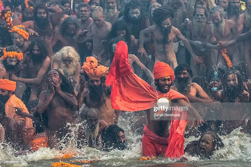 Naga sadhus run in to bathe in the waters of the holy Ganges river during the auspicious bathing day of Makar Sankranti of the Maha Kumbh Mela on January 14, 2013 in Allahabad, India. The Maha Kumbh Mela, believed to be the largest religious gathering on earth is held every 12 years on the banks of Sangam, the confluence of the holy rivers Ganga, Yamuna and the mythical Saraswati. The Kumbh Mela alternates between the cities of Nasik, Allahabad, Ujjain and Haridwar every three years. The Maha Kumbh Mela celebrated at the holy site of Sangam in Allahabad, is the largest and holiest, celebrated over 55 days, it is expected to attract over 100 million people.