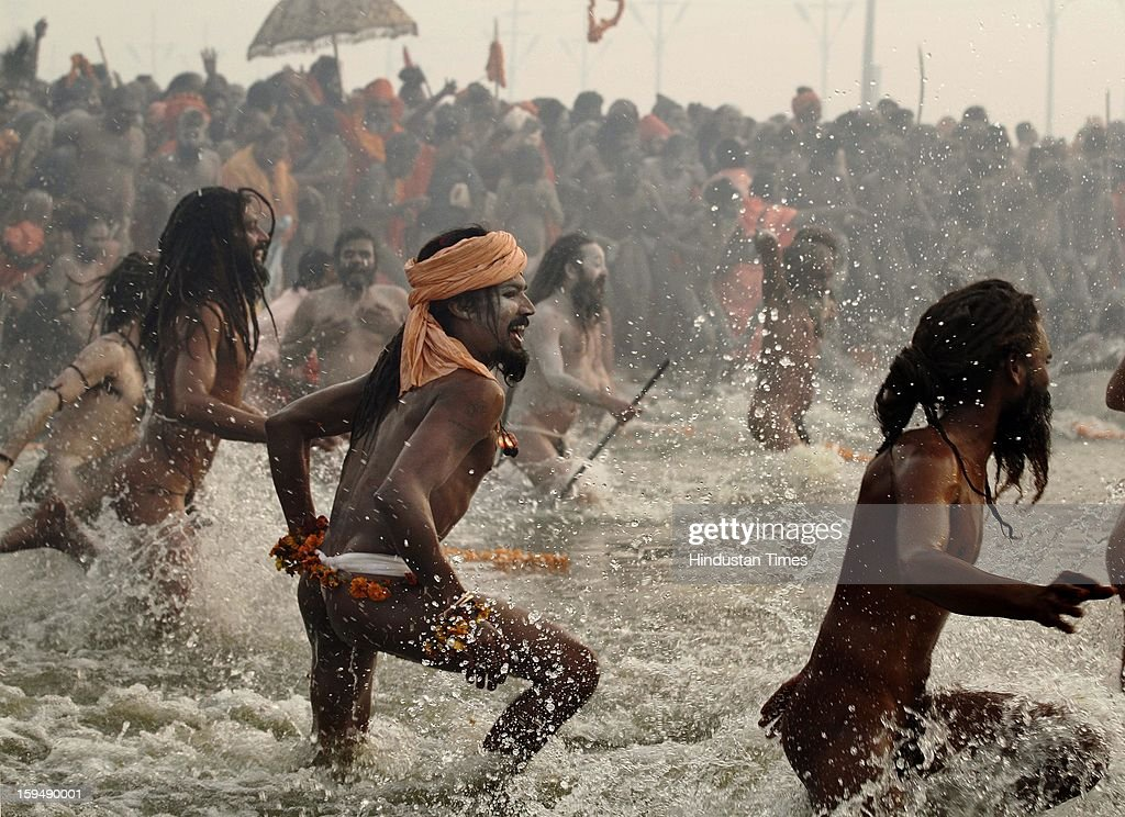 Naga Sadhus take Shahi Snan (royal bath) at the bank of Sangam confluence of river Ganga, Yamnuna and mythical Saraswati on the occasion of Makar Sankranti on January 14, 2013 in Allahabad, India. Kumbh is World's biggest religious gathering, in which more that 100 million of Hindus and sikh devotees will take part over next 55 days. Apart from being pilgrimage of faith, salvation and hope for millions of devotees, it also serve as meeting ground for the vast spectrum of Indian religious and spiritual views.