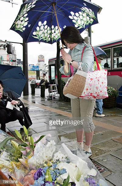 A woman offers a flower bouquet and prays at the murder site of Nagasaki Mayor Iccho Ito in Nagasaki city Japan's soputhern island of Kyushu 18 April...