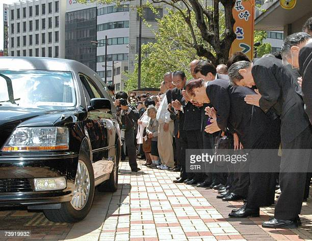 City employees and city coucil members pay their final respects the slain Mayor of Nagasaki Iccho Ito facing a black hearse carrying his body in...