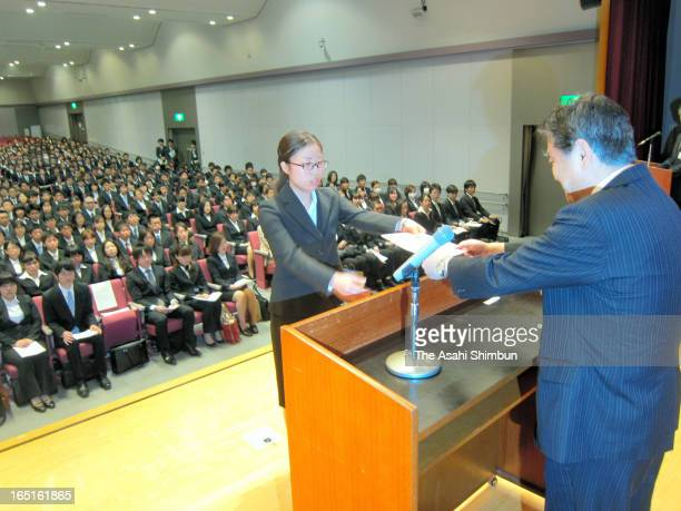 Nagoya City mayor Takashi Kawamura passes a certificate of employment to a new employee during the welcome ceremony on April 1 2013 in Nagoya Aichi...