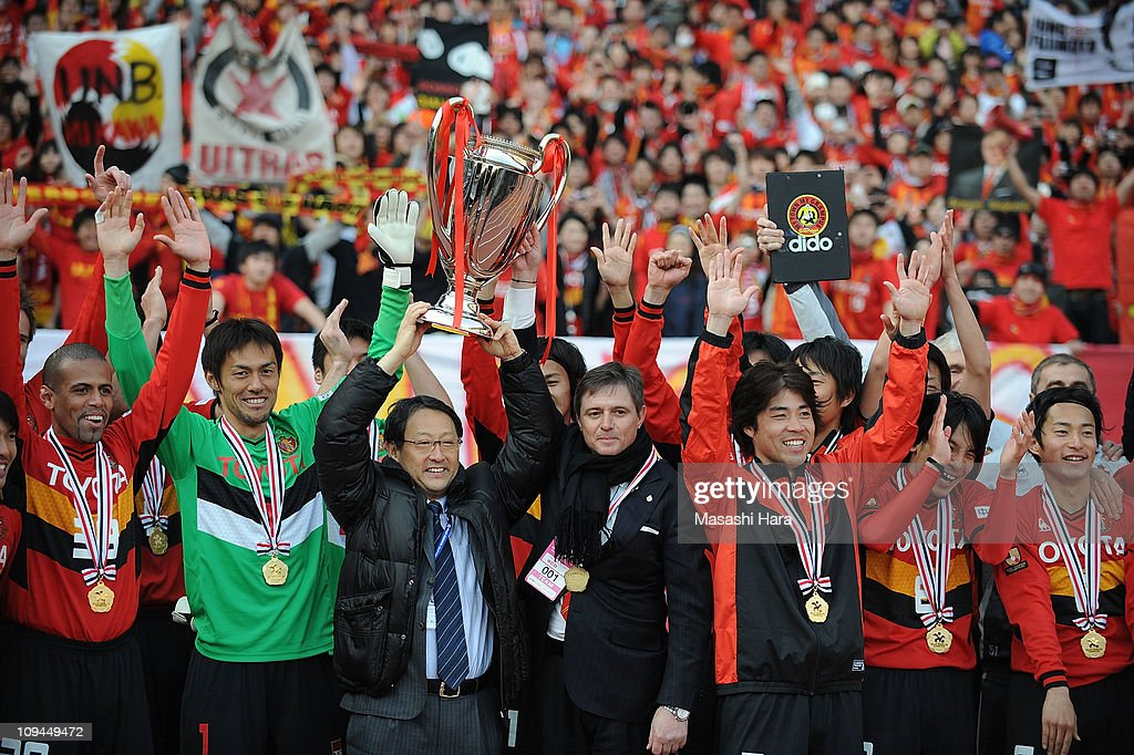 Nagoya Grampus players celebrate with Toyota Motor Corporation President Akio Toyoda (3L) and Nagoya Grampus head coach Dragan Stojkovic (4L) after winning the Fuji Xerox Super Cup match between Nagoya Grampus and Kashima Antlers at Nissan Stadium on February 26, 2011 in Yokohama, Japan.