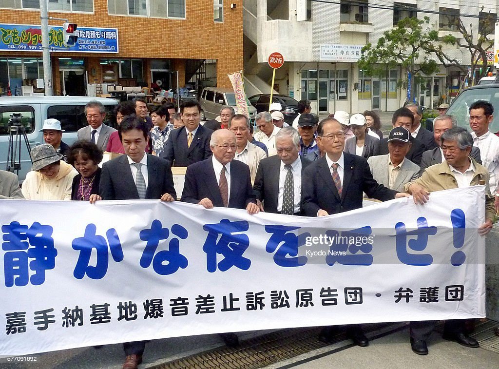 Naha Japan Plaintiffs and their supporters holding a banner that reads ''give us back our peaceful nights'' enter the Okinawa branch of the Naha...