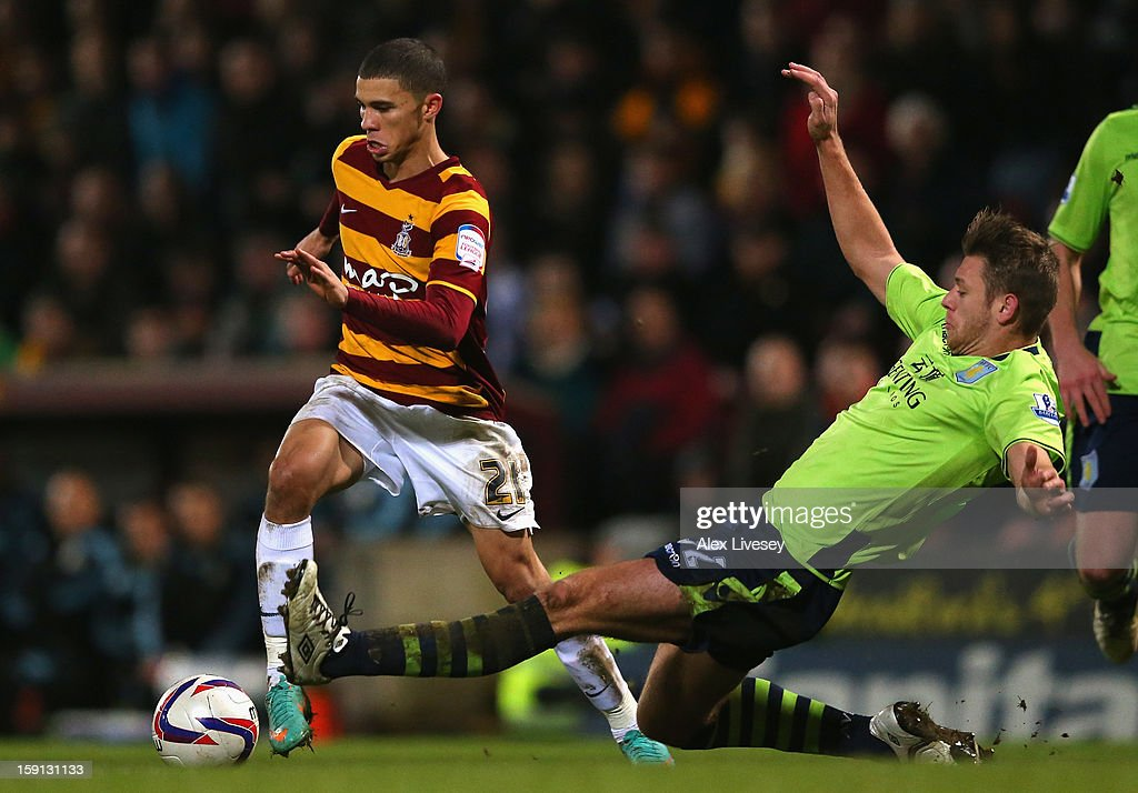 Nahki Wells of Bradford City beats a challenge from Nathan Baker of Aston Villa during the Capital One Cup Semi-Final 1st Leg match between Bradford City and Aston Villa at Coral Windows Stadium, Valley Parade on January 8, 2013 in Bradford, England.