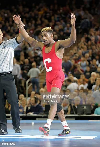 Nahshon Garrett of the Cornell Big Red gets his hand raised after winning his match against Cory Clark of the Iowa Hawkeyes during the finals of the...