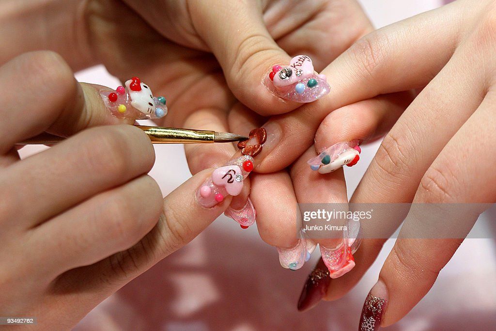 A nail artist decorates visitor's nails during the Tokyo Nail Expo 2009 at Tokyo Big Sight on November 30, 2009 in Tokyo, Japan. The nail industry has grown to nearly 200 million Japanese yen market in 2008 and the annual event attracts 50,000 visitor.
