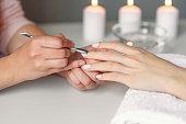 Closeup of beautiful woman hands getting manicure in spa salon.