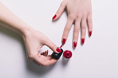 Woman polish her nails with red polish color on a white background. Above view