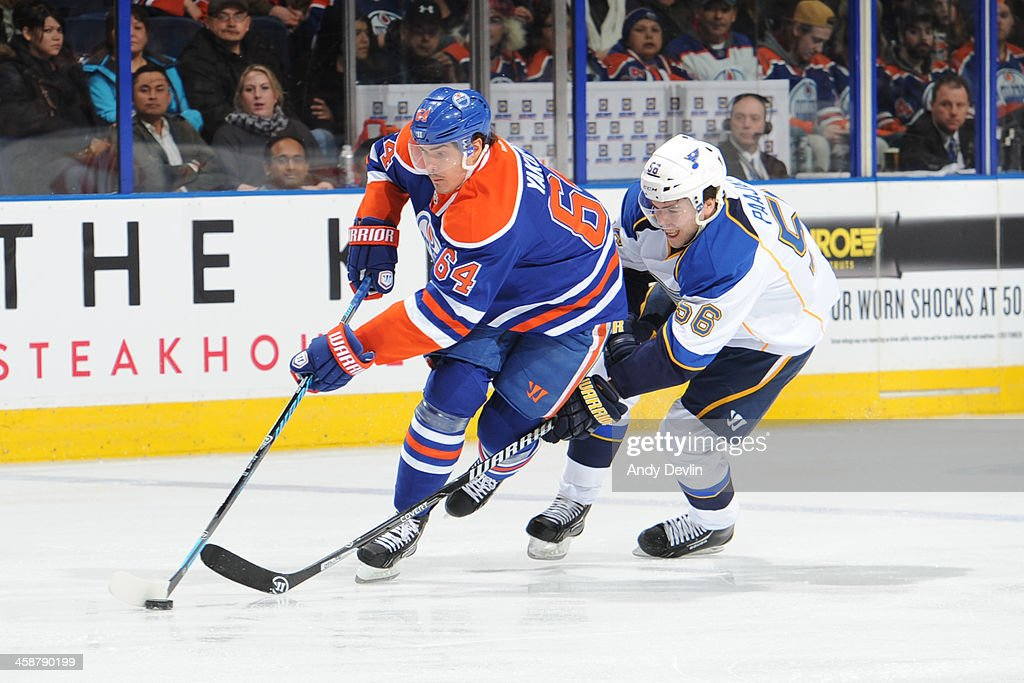 Nail Yakupov #64 of the Edmonton Oilers battles for the puck against Magnus Paajarvi #56 of the St. Louis Blues on December 21, 2013 at Rexall Place in Edmonton, Alberta, Canada.