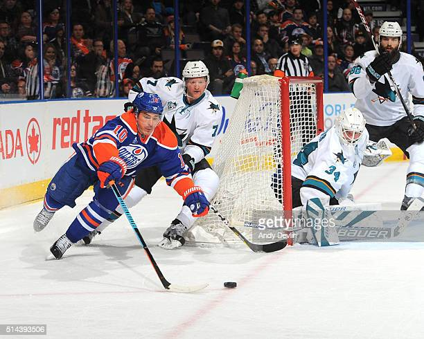 Nail Yakupov of the Edmonton Oilers battles for the puck against Paul Martin of the San Jose Sharks on March 8 2016 at Rexall Place in Edmonton...