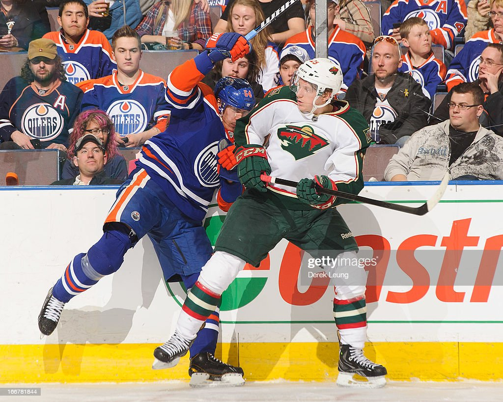 Nail Yakupov #64 of the Edmonton Oilers collides with Jonas Brodin #25 of the Minnesota Wild during an NHL game at Rexall Place on April 16, 2013 in Edmonton, Alberta, Canada.
