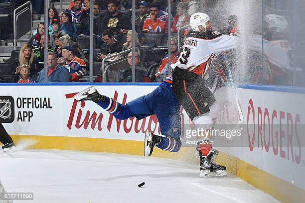 Nail Yakupov of the Edmonton Oilers goes flying into the boards during a battle for the puck against Clayton Stoner of the Anaheim Ducks on October 4...