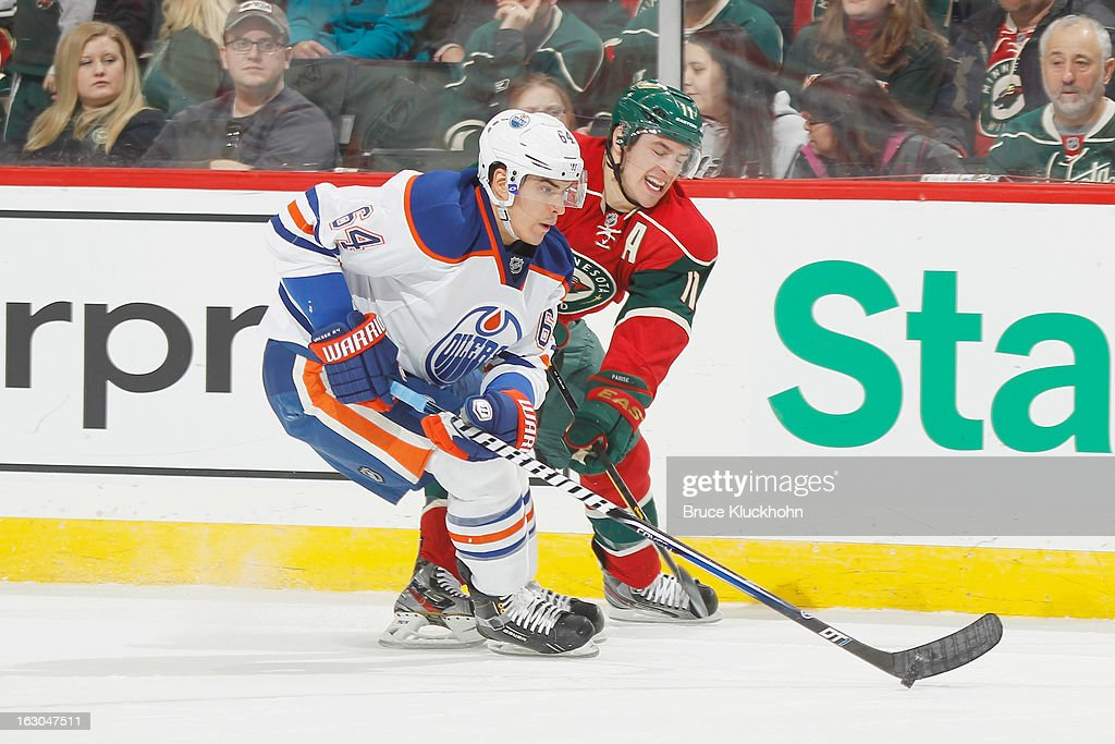 <a gi-track='captionPersonalityLinkClicked' href=/galleries/search?phrase=Nail+Yakupov&family=editorial&specificpeople=7419136 ng-click='$event.stopPropagation()'>Nail Yakupov</a> #64 of the Edmonton Oilers handles the puck with <a gi-track='captionPersonalityLinkClicked' href=/galleries/search?phrase=Zach+Parise&family=editorial&specificpeople=213606 ng-click='$event.stopPropagation()'>Zach Parise</a> #11 of the Minnesota Wild defending during the game on March 3, 2013 at the Xcel Energy Center in Saint Paul, Minnesota.