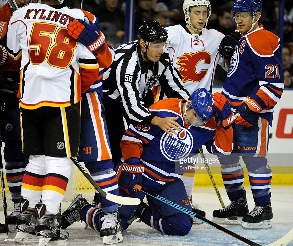 Nail Yakupov #10 of the Edmonton Oilers is rescued from a scrum by an NHL official during a game against the Calgary Flames at Rexall Place on September 21, 2015 in Edmonton, Alberta, Canada.