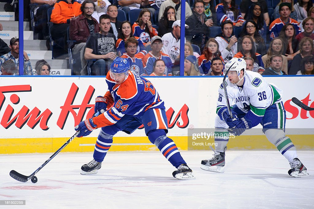 <a gi-track='captionPersonalityLinkClicked' href=/galleries/search?phrase=Nail+Yakupov&family=editorial&specificpeople=7419136 ng-click='$event.stopPropagation()'>Nail Yakupov</a> #64 of the Edmonton Oilers skates with the puck past the defence of <a gi-track='captionPersonalityLinkClicked' href=/galleries/search?phrase=Jannik+Hansen&family=editorial&specificpeople=741716 ng-click='$event.stopPropagation()'>Jannik Hansen</a> #36 of the Vancouver Canucks during a preseason NHL game at Rexall Place on September 21, 2013 in Edmonton, Alberta, Canada.