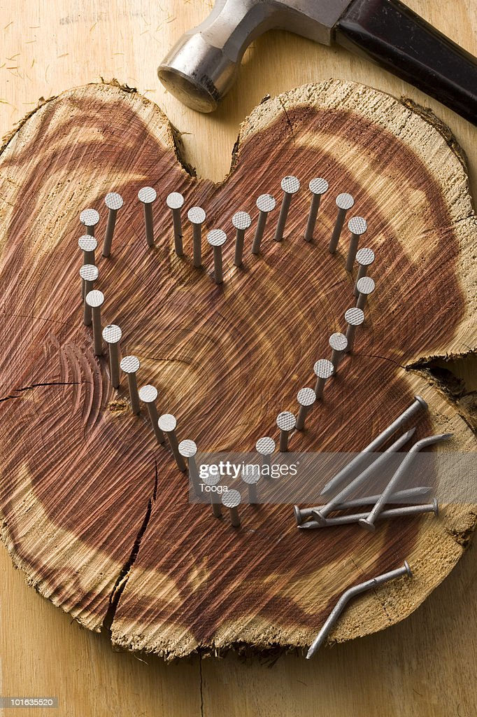 Nails hammered into wood to make a heart : Stock Photo