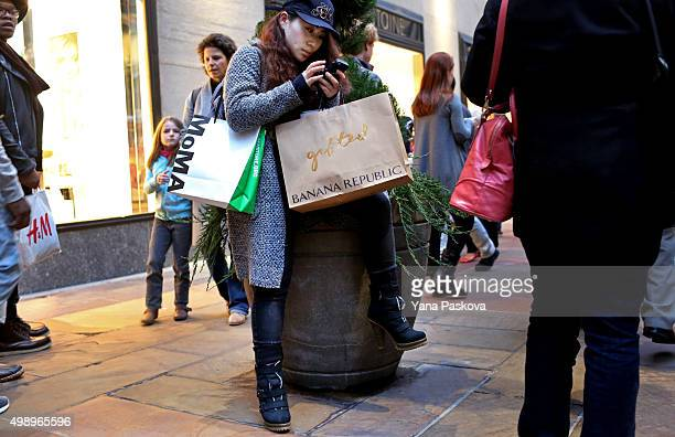 Naima Hsu visiting from China rests with her shopping bags on a plant at Rockefeller Center in New York City on Black Friday November 27 2015...