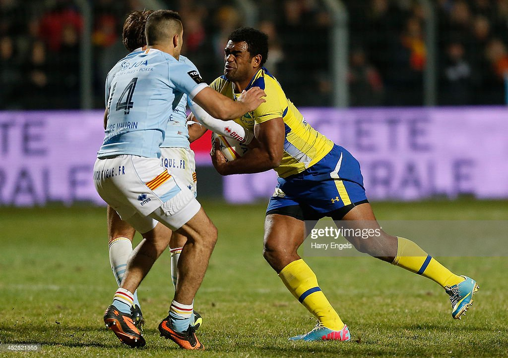 Naipolioni Nalaga of ASM Clermont Auvergne is tackled by the Perpignan defence during the Top 14 match between Perpignan and ASM Clermont Auvergne at Stade Aime Giral on November 29, 2013 in Perpignan, France.