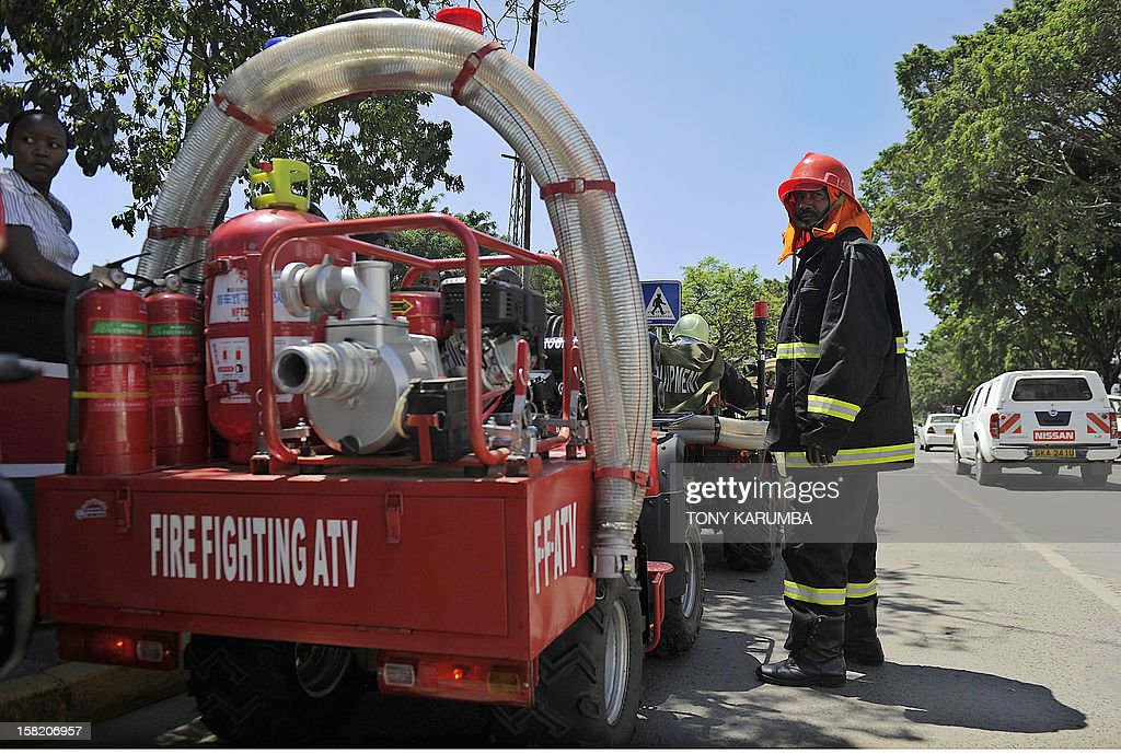 A Nairobi Fire Brigade serviceman stands next to a Fire Fighting All-Terrain-Vehicle (ATV) on December 11, 2012 in Nairobi which is the latest effort by the East African nation's government to beef up it's preparedness to respond to and curb fire, particularly in slums where fire outbreaks have in recent years claimed numerous lives and property due to their unregulated rapid growth making them less accessible to traditional fire fighting engines. At least 120 people burned to death when a pipeline burst into flames in a Nairobi slum in September 2011 as local people were siphoning fuel from it, and more than 100 were injured. AFP PHOTO/Tony KARUMBA