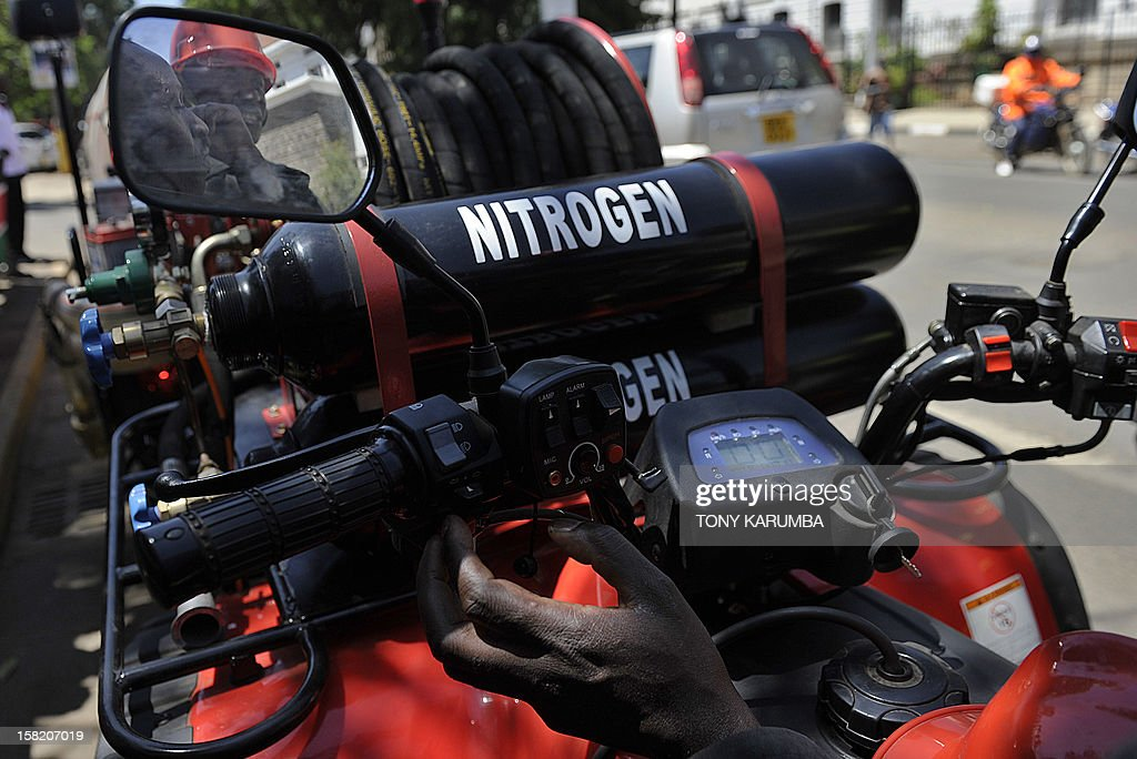Nairobi Fire Brigade servicemen are reflected in the miorror of a Fire Fighting All-Terrain-Vehicle (ATV) on December 11, 2012 in Nairobi which is the latest effort by the East African nation's government to beef up it's preparedness to respond to and curb fire, particularly in slums where fire outbreaks have in recent years claimed numerous lives and property due to their unregulated rapid growth making them less accessible to traditional fire fighting engines. At least 120 people burned to death when a pipeline burst into flames in a Nairobi slum in September 2011 as local people were siphoning fuel from it, and more than 100 were injured. AFP PHOTO/Tony KARUMBA