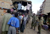 Suspected Mungiki adherents are loaded onto a police truck 07 June 2007 after they were rounded up during a police crackdown on the banned Mungiki...