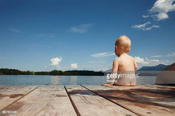 naked baby boy sitting at lake on boardwalk