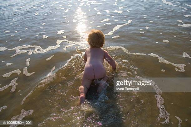 Naked baby girl (9-12 months) crawling through water