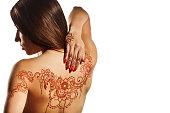 naked back of young girl with henna mehendi on white backround