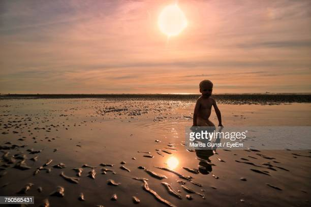 Naked Boy At Beach Against Sky During Sunset