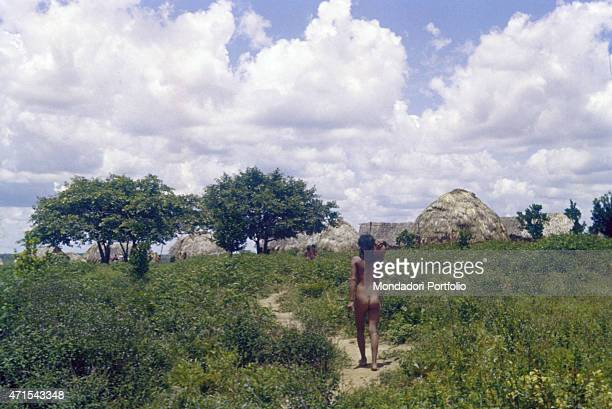 'A naked girl going towards a village of huts the girl belongs to the indigenous people Xavante of the Brazilian state of Mato Grosso Brazil 12th...