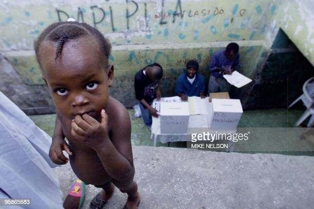 A naked Haitian girl stands as poll workers prepare for voters to cast their ballots in PortauPrince Haiti as presidential and senatorial elections...