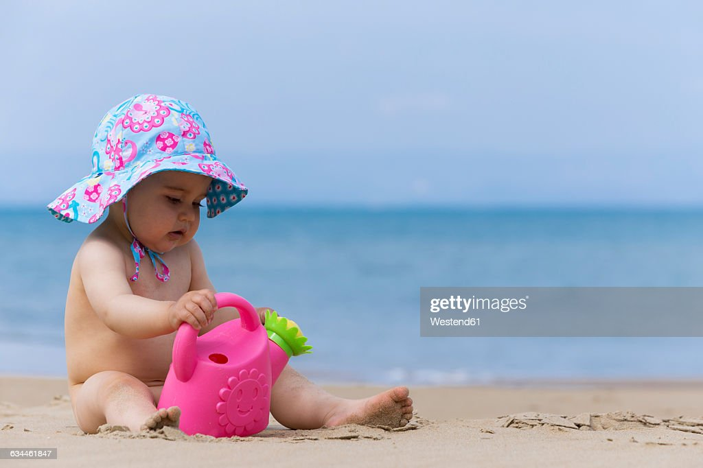 Naked Little Baby Girl Wearing Summer Hat Playing On The