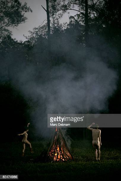 Naked man and woman dancing around a fire