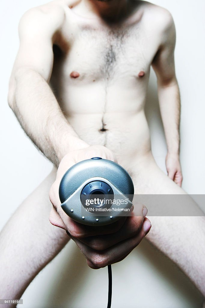 Naked man holding a web camera in front of his genitals : Stock Photo
