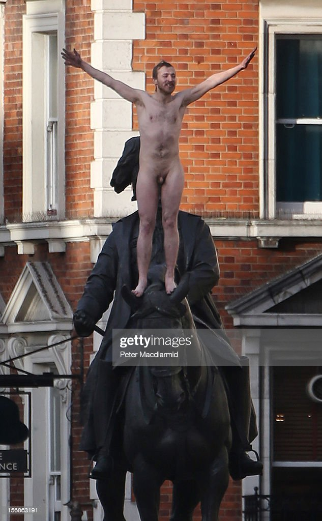 A naked man stands at the top of a statue in Whitehall as police cordon the area off on November 23, 2012 in London, England. The incident in central London has brought traffic to a standstill as Police attempted to talk the man down from the Duke of Cambridge statue outside the Ministry of Defence building.