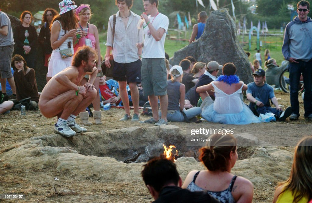 A naked man warms himself by the fire within the stone circle during the Glastonbury Music Festival held at Worthy Farm on June 24, 2005 in Glastonbury, England.