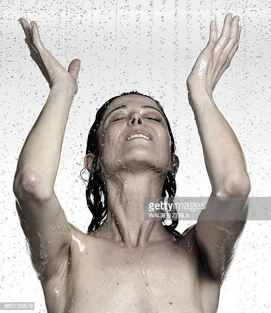 Naked mature woman showering with hands raised