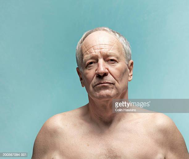 Naked senior man against blue background, portrait