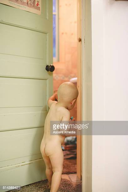Naked toddler opens door, peers into room