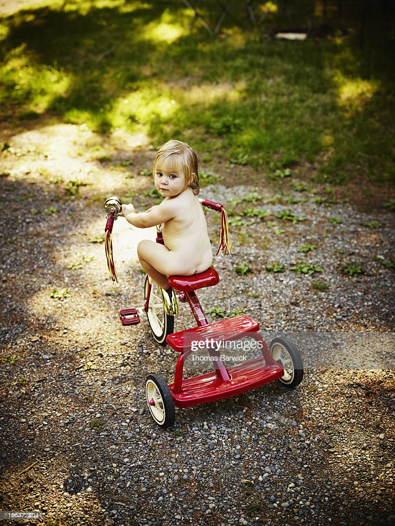 Naked toddler sitting on tricycle in backyard : Stock Photo