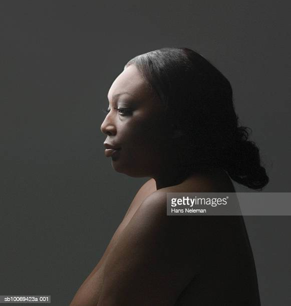 Naked woman against grey background, looking away