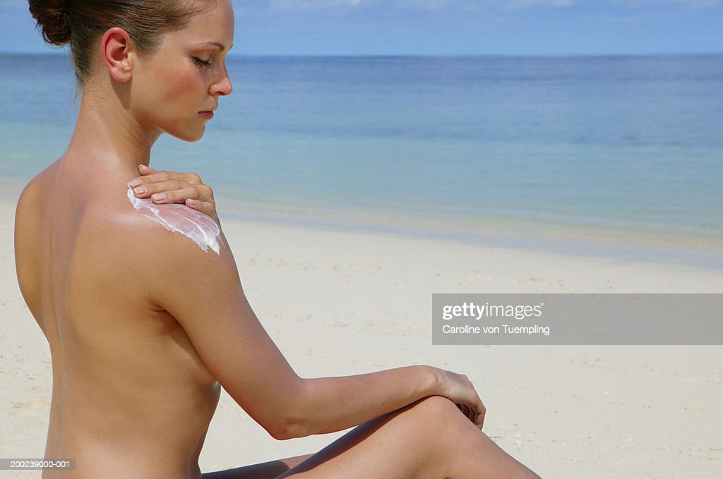 Naked woman applying sunscreen on beach, side view : Stock Photo
