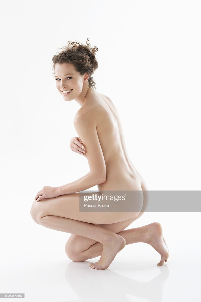 Naked woman covering her breasts and smiling : Stock Photo