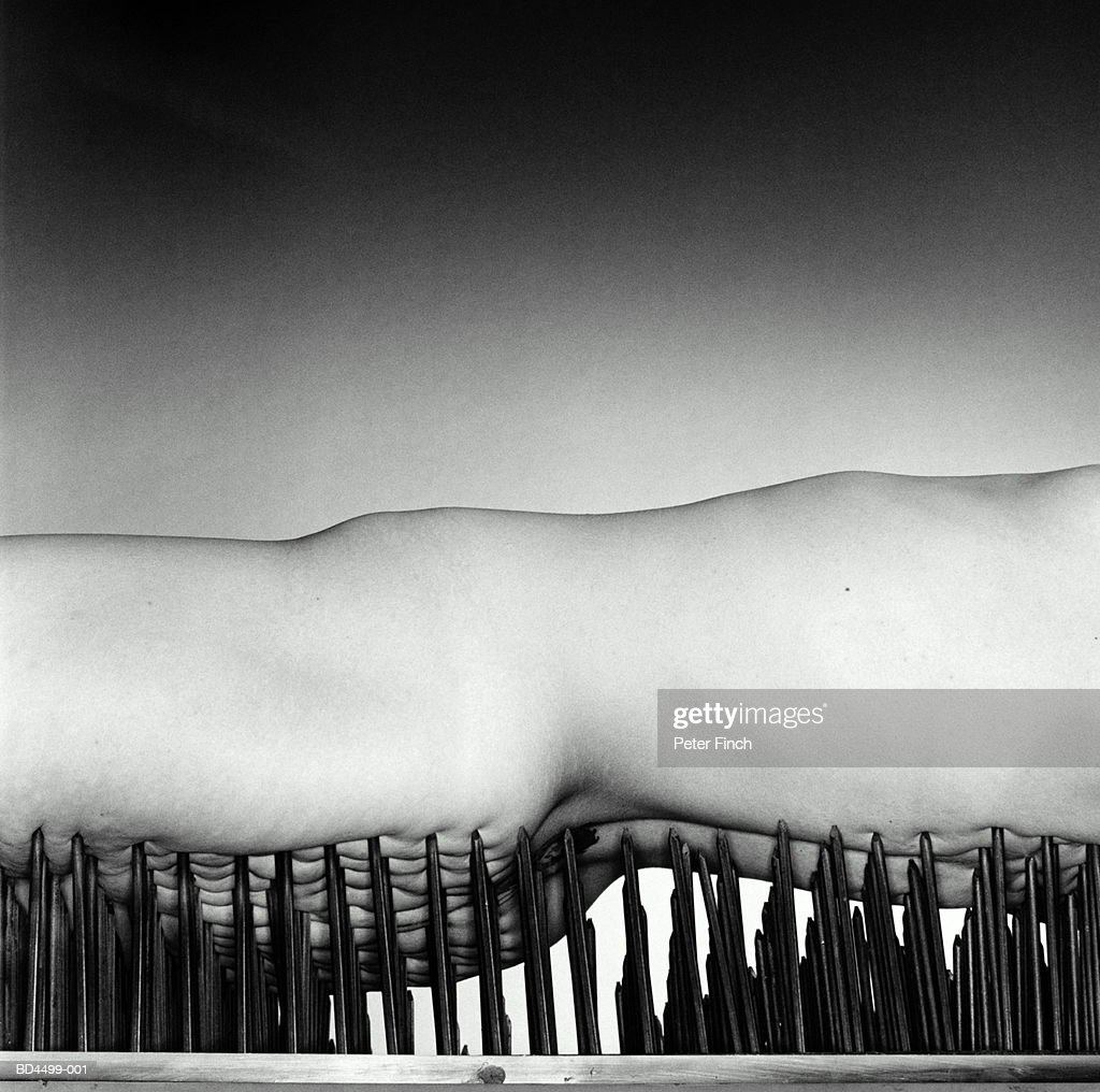 Naked woman lying on bed of nails, mid section, close-up (B&W) : Stock Photo