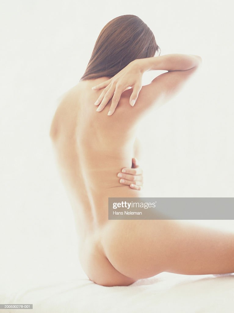 Naked woman rubbing back, rear view : Stock Photo