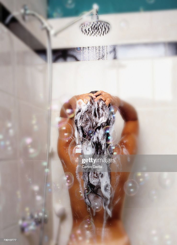 Naked woman showering in bathroom, rear view : Stock Photo
