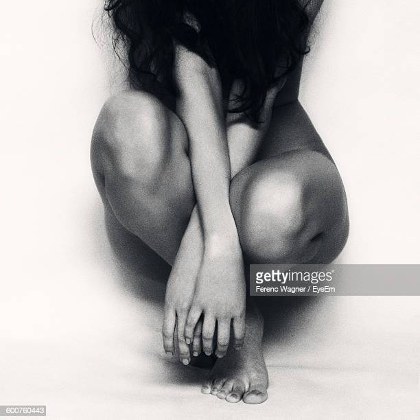 Naked Woman Sitting Against White Background